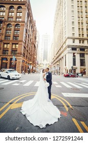 Elegant bride in a white dress and veil. Handsome groom in a blue suit. Couple in a big city
