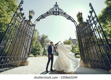 Elegant bride in a white dress and veil. Handsome groom in a blue suit. Couple in a summer park
