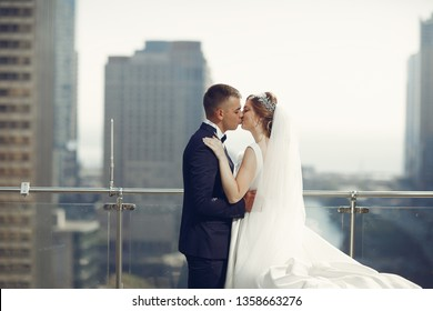Elegant bride in a white dress and veil. Handsome groom in a blue suit. Couple in a big town