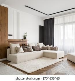 Elegant, bright and comfortable designed living room with big corner sofa, wooden floor and big windows