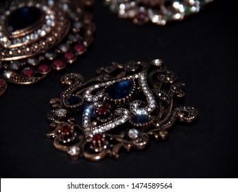 Elegant brooch decorated with the precious stones and isolated on a dark background