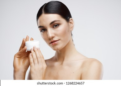 Elegant brunette with bare shoulders with body cream clean skin