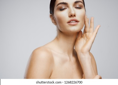 Elegant brunette with bare shoulders holds her hand near the face Cosmetology