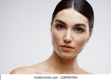Elegant brunette bare-shouldered cosmetology clean skin on a gray background