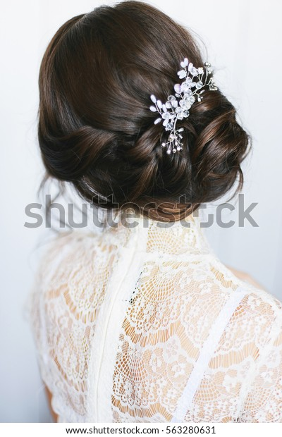 Elegant brunette bride sitting back with collected up do hair. Tender wedding stylish hairstyle with accessories. Fine art wedding. Light bridal morning preparation.