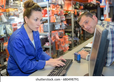 elegant brunette checking parts availability in a garage warehouse