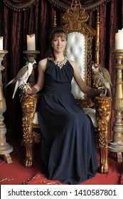 elegant brunette in evening black dress on a throne with falcons on her arm