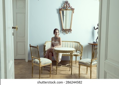 elegant brunette girl in luxury room sitting on vintage sofa with classic hair-style, precious necklace and pink dress. Aristocratic style and antiques furnitures