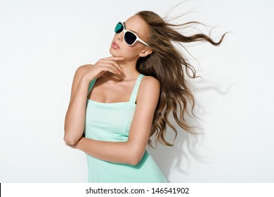 elegant brunette in mint dress and sunglasses posing in the studio