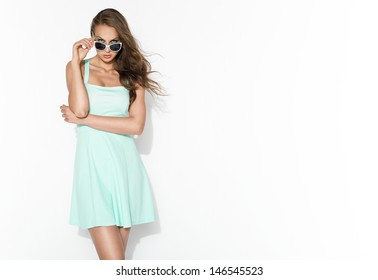 elegant brunette in mint dress and sunglasses posing in the studio