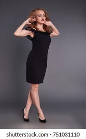 Elegant brunette posing in black beautiful dress with open shoulders