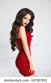 Elegant brunette sexy woman in fashionable red dress. Attractive girl model with red lips makeup, long wavy hair style isolated on white background.