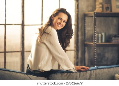 An elegant brunette sitting on the back of sofa in a loft, leaning forward and smiling is looking over her shoulder. In the background, the daylight is streaming through a window. Chic loft.