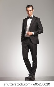 elegant business man in tuxedo standing with open coat on grey studio background