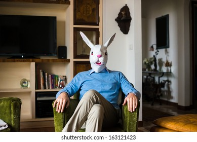 elegant business multitasking rabbit mask man using devices at home