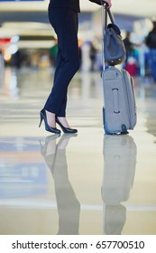 Elegant business woman with hand luggage in international airport terminal. Cabin crew member with suitcase. Unrecognizable person, closeup of legs