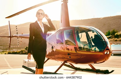 Elegant business woman near the helicopter. Business, success and luxury concept
