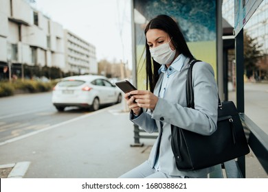 Elegant business woman with protective mask sitting alone on empty street and waiting for bus or taxi transport while using phone. Corona virus or Covid-19 lifestyle concept.