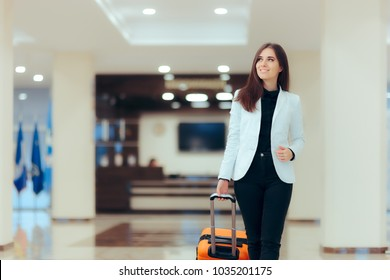 Elegant Business Woman with Travel Trolley Luggage in Hotel Lobby. Female executive with suitcase in work related business trip