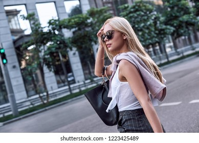 Elegant business woman wearing sunglasses at summer day in the city. She is crosses the road. Side view