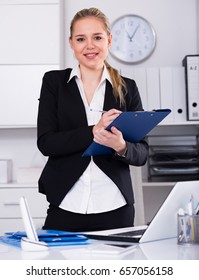 Elegant business woman writing down tasks in office