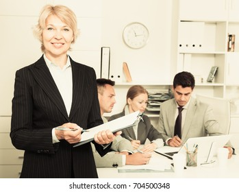 Elegant business woman writing down ideas and tasks on background with team