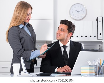 Elegant business woman writing down tasks of chief man at table