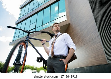 Elegant businessman with bicycle standing against modern business center exterior in front of camera while leaving work and going home