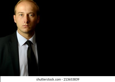 elegant businessman with blonde hair standing in the shade