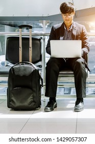 Elegant businessman checking e-mail on mobile phone while walking with suitcase inside airport, experienced male employer using cell telephone while waiting for taxi car coming before work travel