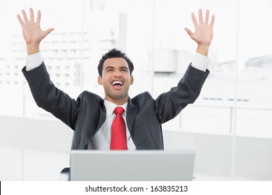 Elegant businessman cheering with raised hands in front of laptop at office desk