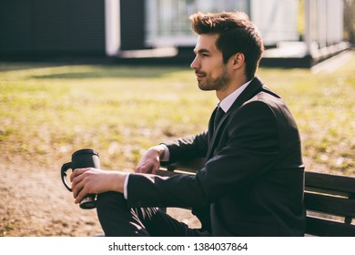 Elegant businessman enjoys drinking coffee while sitting outdoor.Toned image.