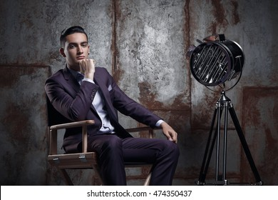 Elegant businessman in fashionable suit posing in the photo studio . luxury portrait of a man sitting in the director's chair next to the model is a retro movie spotlight