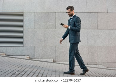 Elegant businessman hand holding and using a smart phone outdoors.