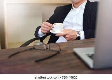 Elegant businessman has a rest with a cup of coffee in his office