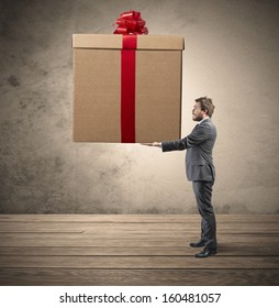 Elegant businessman holding a big Christmas present