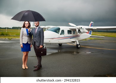 Elegant businessman holding umbrella over himself and his partner with airplane on background