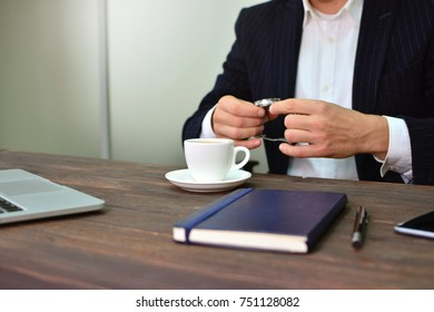 Elegant businessman holds watch in his hands for coffee. Business and time concept.