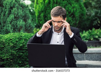 Elegant businessman is sitting with his computer and working. He has got a problem. He is trying to solve them