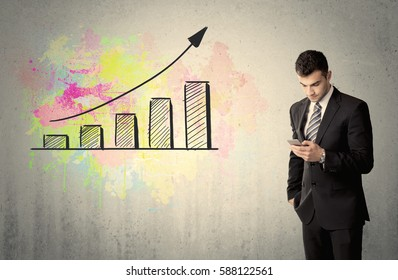 An elegant businessman standing in front of a grey wall with colorful growing chart drawing concept