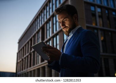 Elegant businessman in suit browsing tablet seriously while standing on dark street in twilight