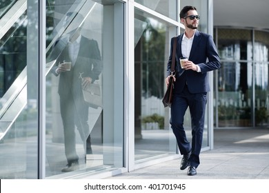 Elegant businessman with take-out coffee going to work