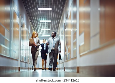Elegant businessman talking to female colleague while both going along corridor