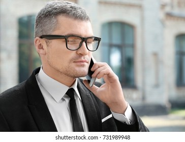 Elegant businessman talking on mobile phone outdoors