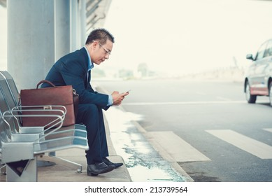 Elegant businessman texting while sitting at the bus stop in the airport