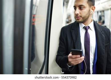 Elegant businessman traveling by metro with gadget