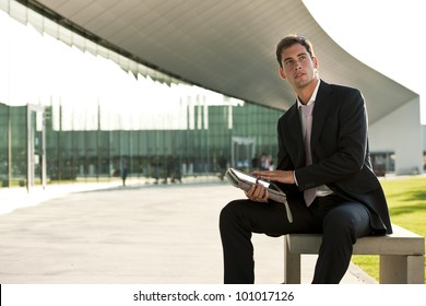 Elegant businessman using hi PC tablet while sitting on a benc outdoors