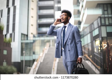 Elegant businessman walking in the street while taking at the phone