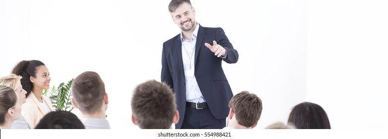 Elegant businessman in white space giving a speech to a group of enthusiastic young people