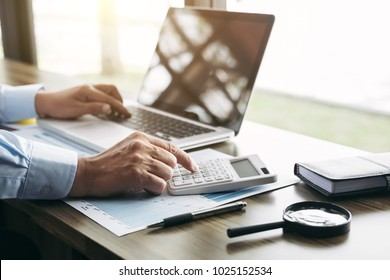 Elegant businessman working on his laptop in a coffee shop, analyzing data and graph, using calculator calculate, young man typing on computer sitting at wooden table.